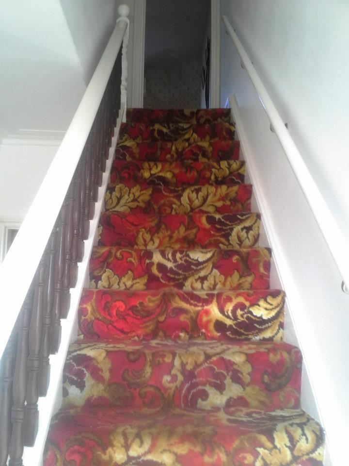 Stairs with a deep red flowered carpet
